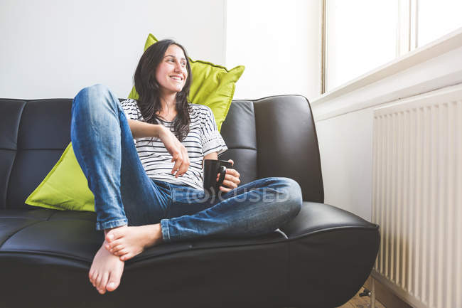 Woman sitting on sofa holding coffee cup looking out of window smiling — Stock Photo