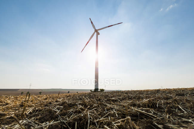 Wind turbine on against sunlight on field — Stock Photo