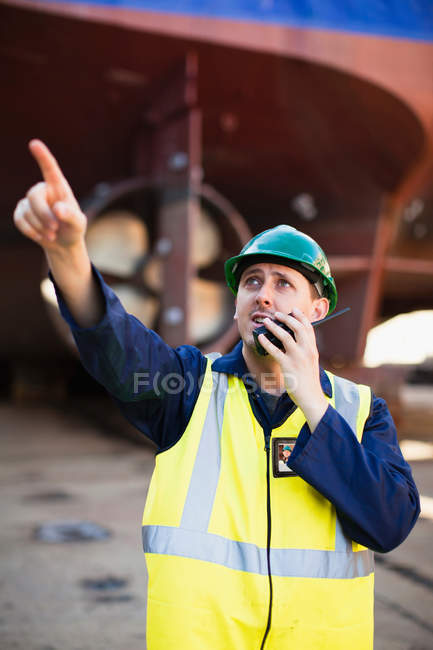 Worker using walkie talkie on dry dock — Stock Photo