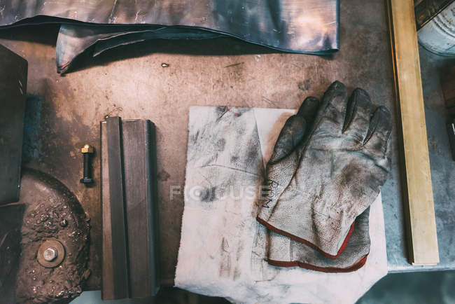Top view of metals and protective gloves on forge workbench — Stock Photo