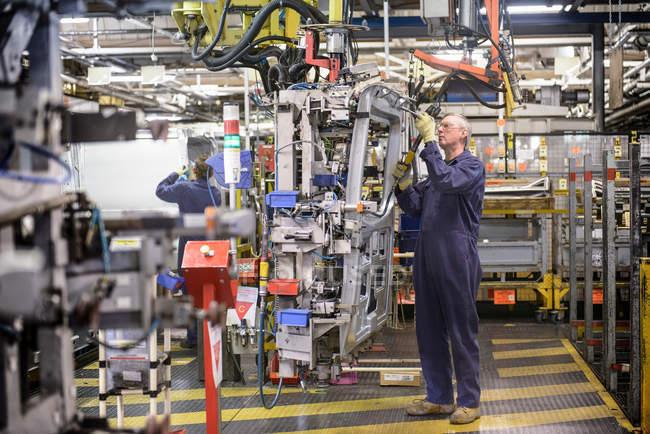 Travailleurs automobiles assemblant le véhicule dans l'usine automobile — Photo de stock