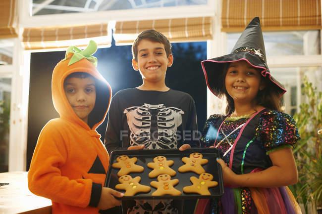 Hermanos y hermanas con disfraces de halloween sosteniendo bandeja de hombres de jengibre - foto de stock