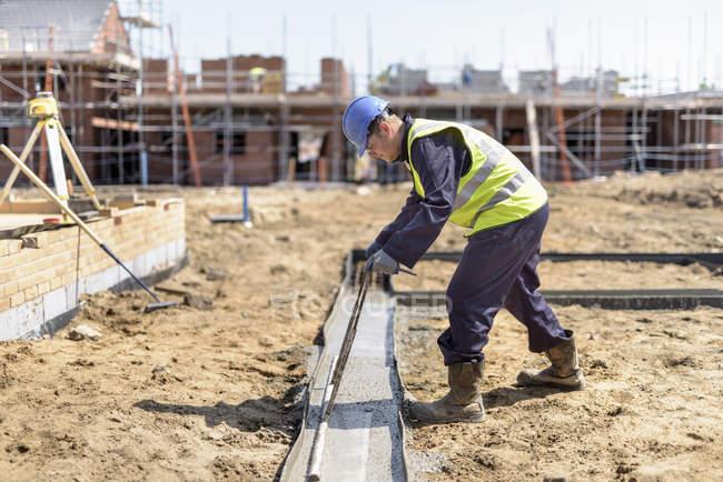 Ученик строителя кладет бетонные фундаменты на строительной площадке — стоковое фото