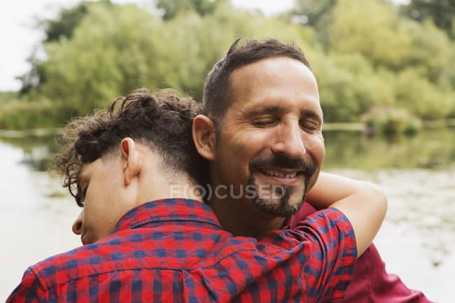 Verticale de père et fils, à l'extérieur, étreignant — Photo de stock