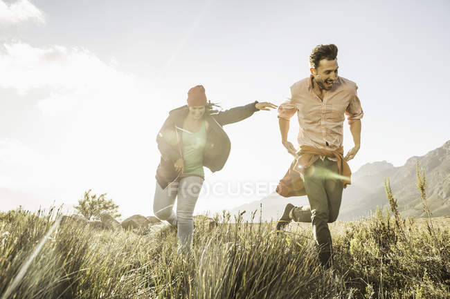 Couple running in field at daytime — Stock Photo