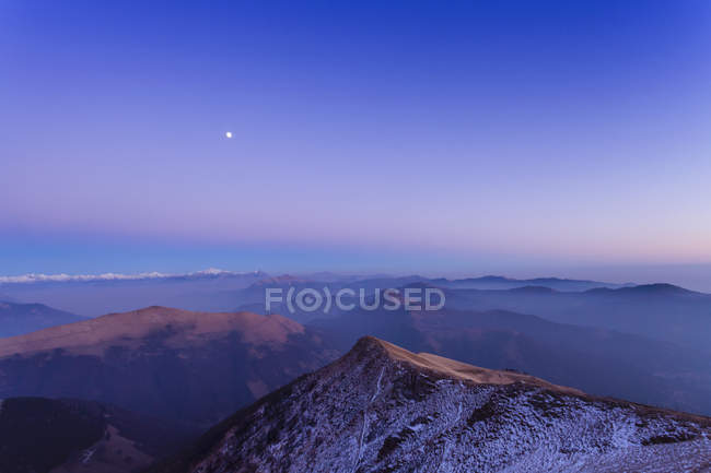 Snowcapped mountain landscape with valley mist at dawn — Stock Photo