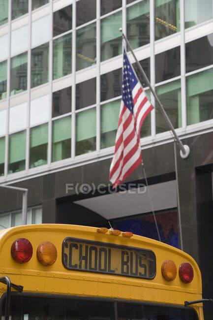 Школьный автобус у офиса с американским флагом, Нью-Йорк, США — стоковое фото
