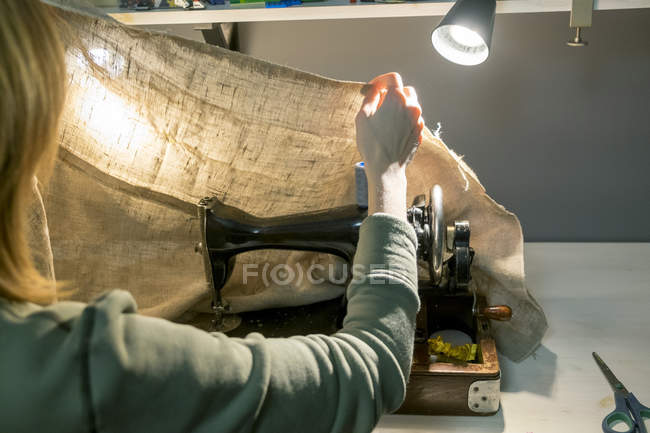 Rear view of seamstress preparing burlap at sewing machine — Stock Photo