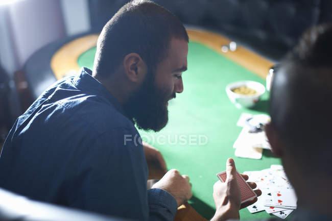 Через плече чоловіки грають у картярські ігри за столом. — стокове фото