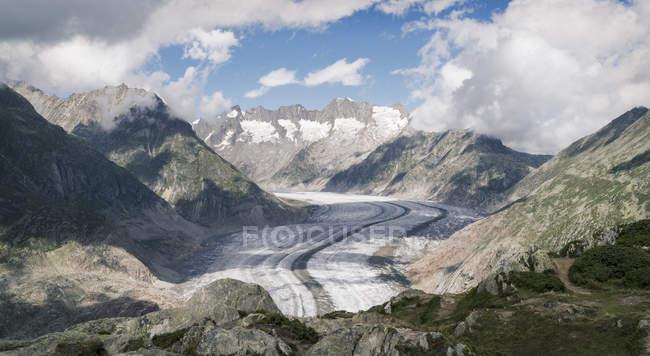 Vale cobertas de neve e montanhas com nuvens baixas na luz solar — Fotografia de Stock