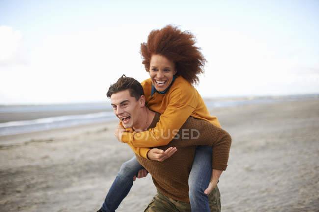 Couple playing piggyback on beach — Stock Photo