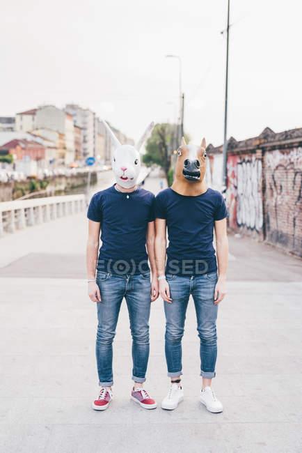 Portrait of two men wearing rabbit and horse masks on urban bridge — Stock Photo