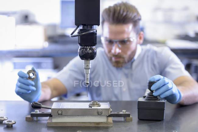 Travailleur mesurant les pièces dans le contrôle de la qualité dans l'usine de pièces automobiles — Photo de stock