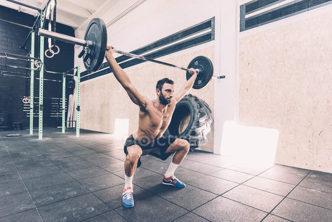 Young man weightlifting barbell in cross training gym — Stock Photo