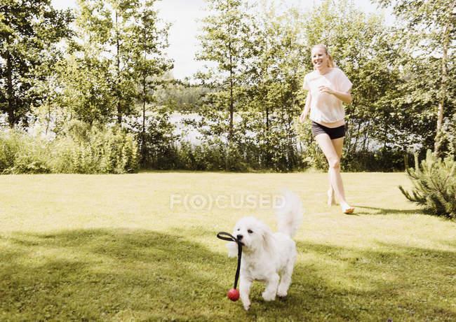 Frau läuft im Garten einem Hund hinterher, orivesi, Finnland — Stockfoto