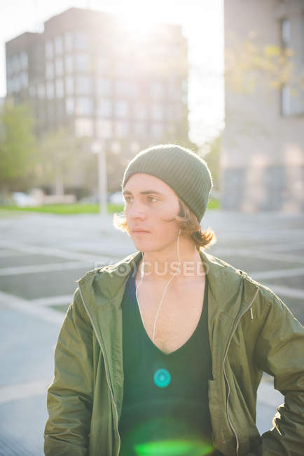 Cool young man wearing knitted hat standing near tower block — Stock Photo