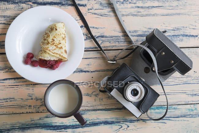 Still life of camera, pancake dessert and cup of milk — Stock Photo
