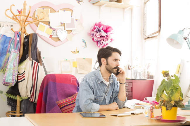 Joven diseñador masculino hablando en smartphone en estudio de prensa de impresión - foto de stock