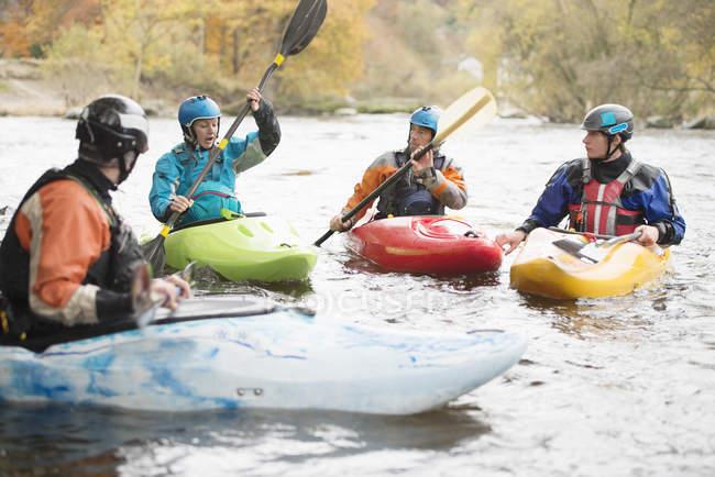 Kayakers masculins et féminins ayant la conversation d'équipe sur la rivière Dee, Llangollen, Pays de Galles du nord — Photo de stock