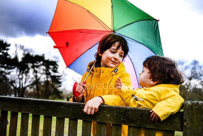Visão aérea de menino e irmão em anoraks amarelos com guarda-chuva no banco do parque — Fotografia de Stock
