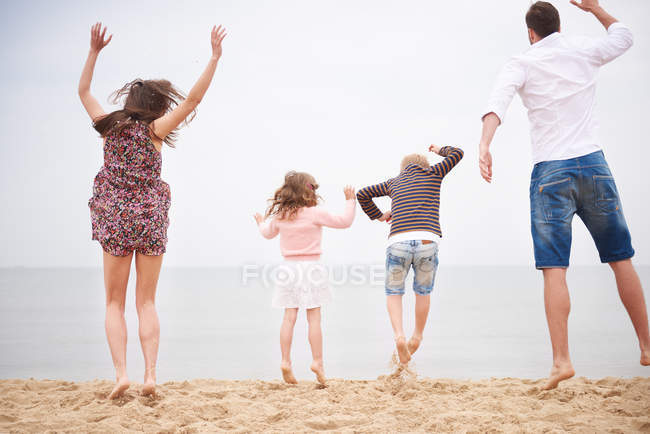 Family jumping on beach against sky together — Stock Photo