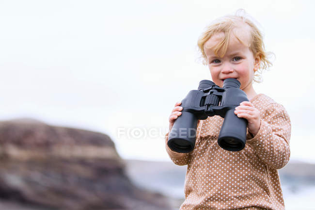 Toddler girl holding binoculars and looking at camera on beach — Stock Photo