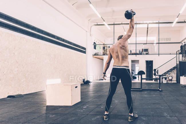 Rückansicht des männlichen cross Trainer Gewichtheben Hanteln im Fitnessstudio — Stockfoto