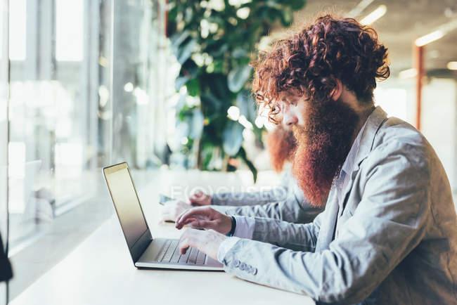 Gemelli hipster maschi che lavorano su laptop alla scrivania dell'ufficio — Foto stock
