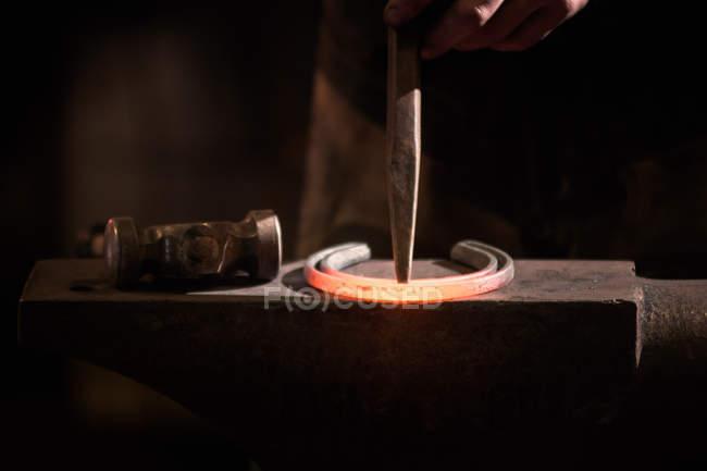 Farrier forging horseshoe on anvil — Stock Photo