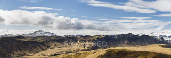 Panoramic view of rocky mountains under blue cloudy sky — Stock Photo
