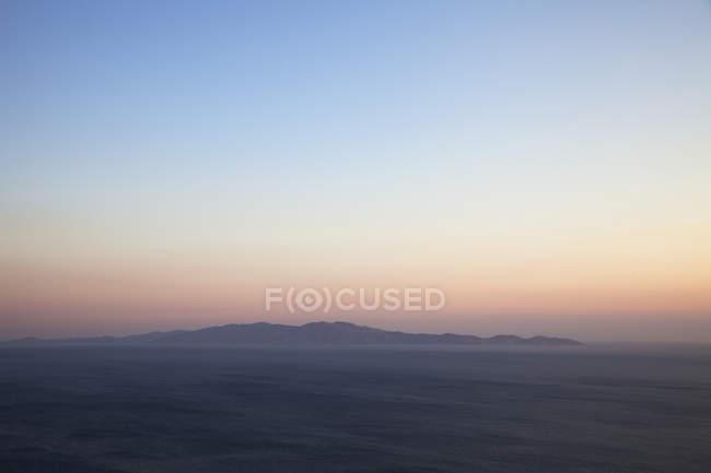 Морський пейзаж і далеких вид на острів Андрос з острові Tinos острова на заході сонця, Греція — стокове фото