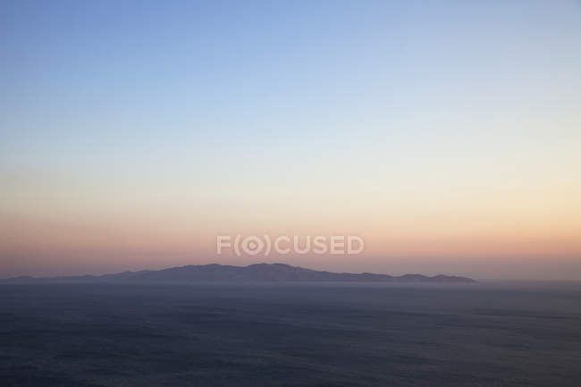 Seascape and distant view of Andros Island from Tinos Island at sunset, Greece — Stock Photo