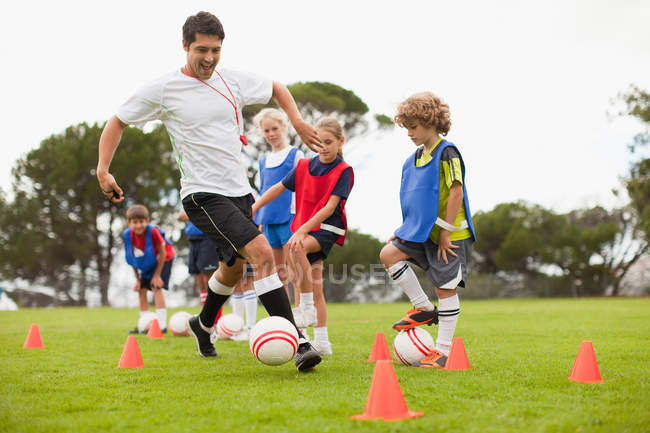 Coach training childrens soccer team — Stock Photo