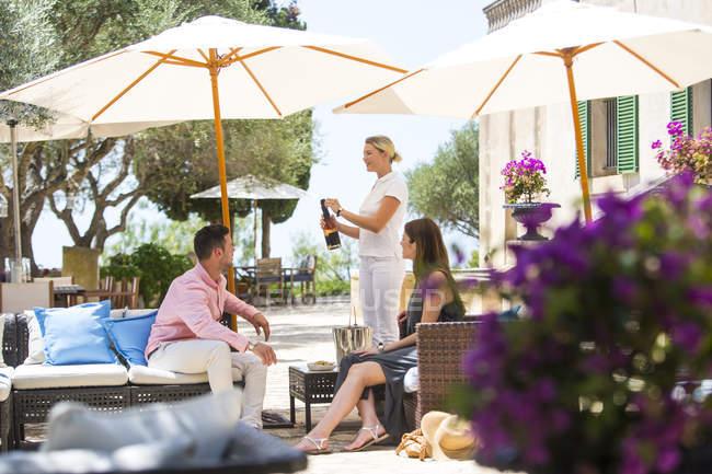 Garçonete abrindo garrafa de champanhe para casal de hóspedes no hotel boutique, Maiorca, Espanha — Fotografia de Stock