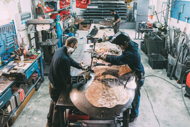 Male metalwork team hammering copper at forge workbench — Stock Photo