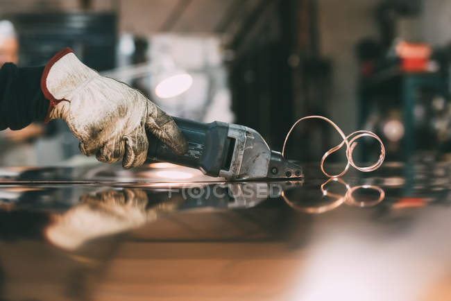 Hands of metalworker cutting copper sheet with electric hand shears at forge workbench — Stock Photo