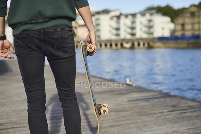 Jeune homme marchant à côté de la rivière, exploitation skateboard, vue arrière, moyenne section, Bristol, Royaume-Uni — Photo de stock