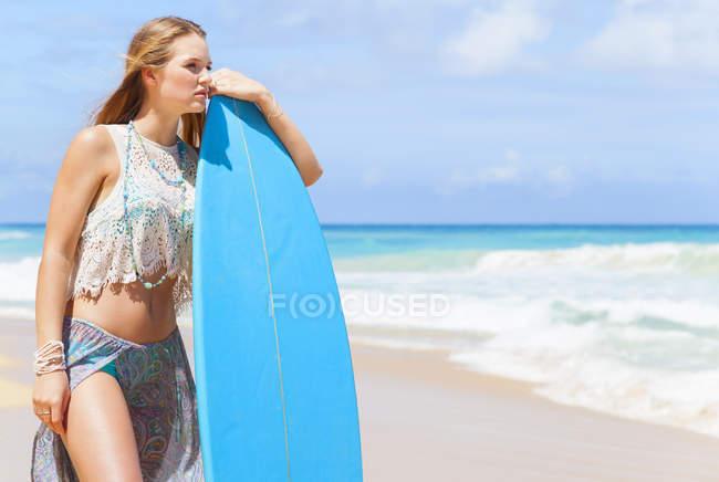 Mujer joven apoyada contra tabla de surf en la playa, República Dominicana, El Caribe - foto de stock