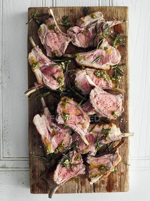 Top view of roasted lamb cutlets on cutting board with  rosemary — Stock Photo