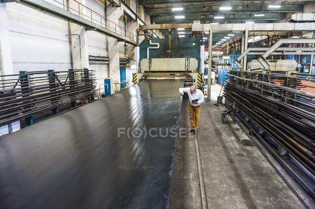 Чоловічий працівник перевірки конвеєрної стрічки в гумовому Роликовий завод — стокове фото