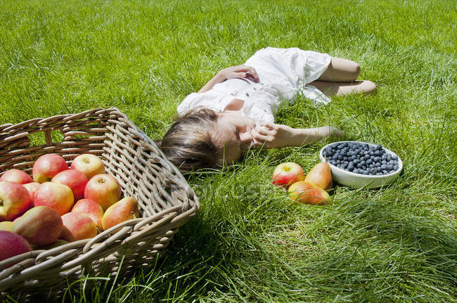 Girl asleep on grass with basket of apples and pears — Stock Photo