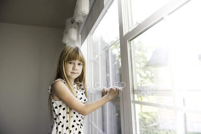 Молодая девушка смотрит в сторону от окна — стоковое фото