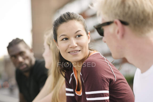 Row of four male and female friends chatting in city skatepark — Stock Photo