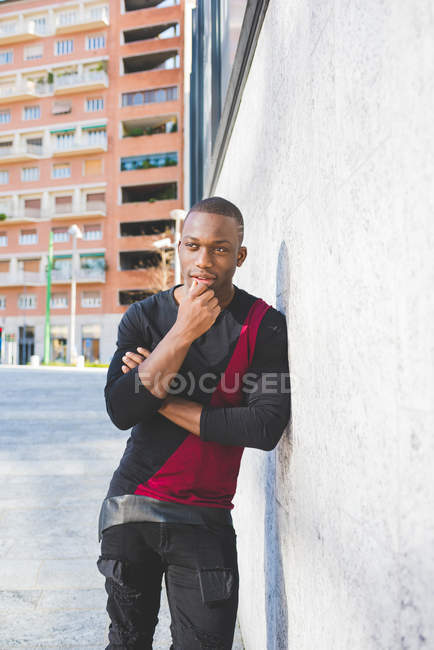 Portrait of young man leaning against wall, hand on chin, thoughtful expression — Stock Photo