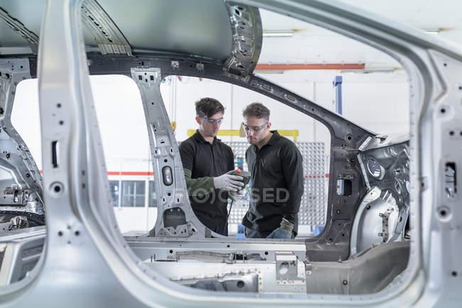 Ученики инженеров по измерению кузова автомобиля на автомобильном заводе — стоковое фото