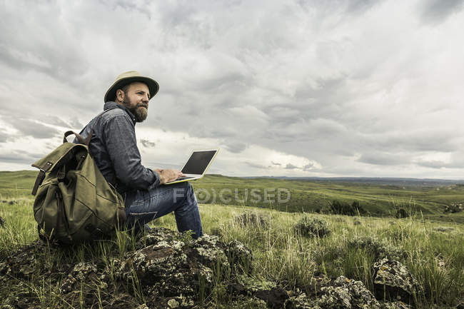 Mature male hiker sitting on rocks with laptop looking out to landscape, Cody, Wyoming, USA — Stock Photo