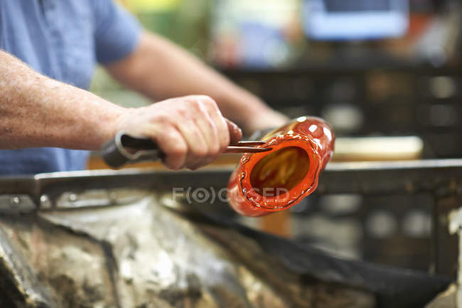 Glassblower in workshop shaping molten glass material with hand tools — Stock Photo
