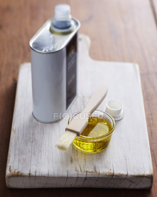 Bol de l'huile d'olive et brosse de pâtisserie sur une planche à découper en bois — Photo de stock