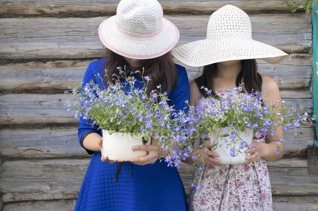 Дві самки носіння капелюшків від сонця, проведення горщиках рослин, приховані лиця — стокове фото