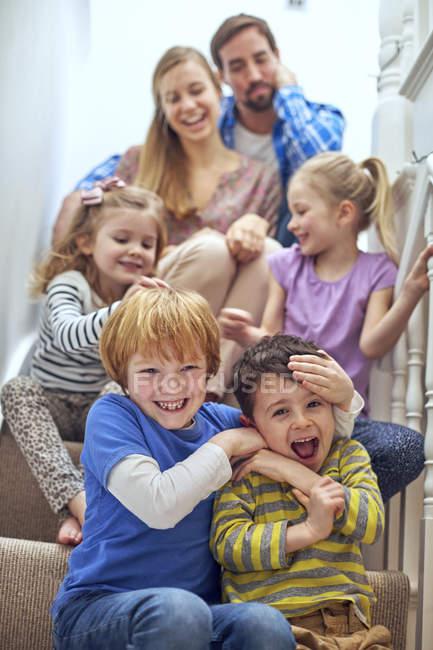 Pais felizes e crianças sentadas na escada — Fotografia de Stock